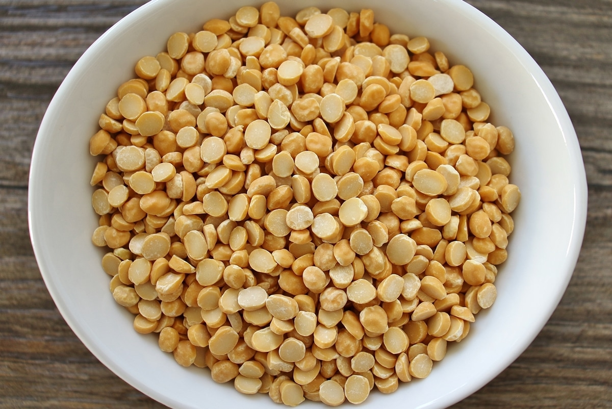 Uncooked chana dal (bengal gram) in a white bowl on a wooden surface.