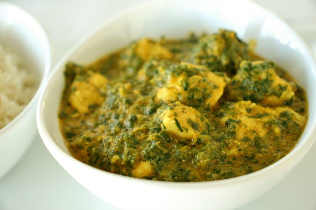 Indian chicken saag spinach curry in a white bowl with a bowl of basmati rice to the side