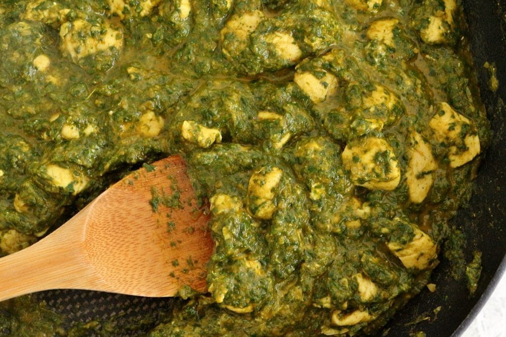 Cooking chicken saag in a frying pan, with a wooden spoon stirring the mixture