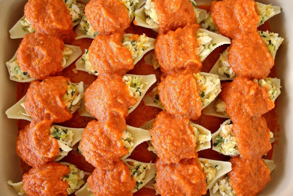 Crab stuffed shells arranged in a rectangular casserole dish topped with tomato sauce