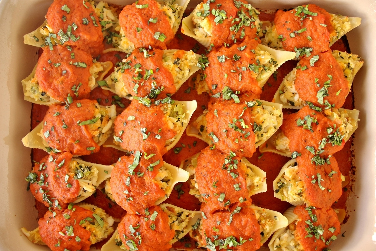 Crab stuffed shells arranged in a rectangular casserole dish, after baking.