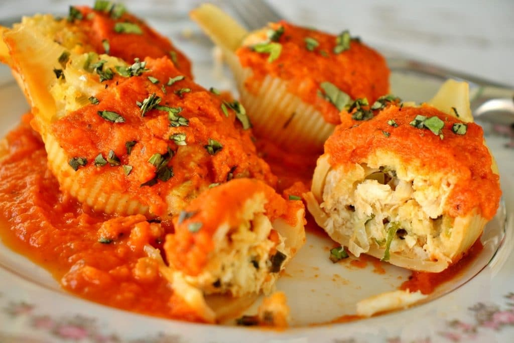 Four crab stuffed shells topped with orange-infused tomato sauce and chopped basil, served on fine china. One shell is cut to show the filling inside.