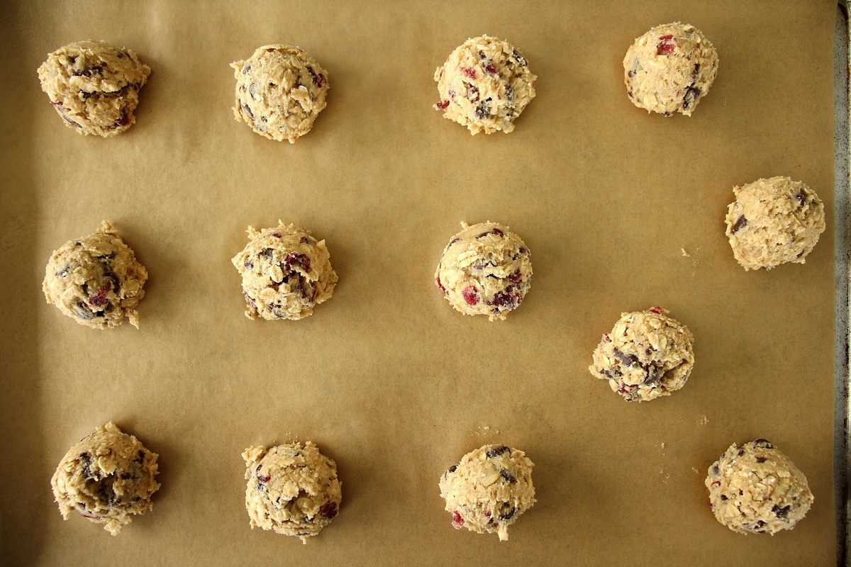 Raw cookie dough scooped onto a parchment lined baking sheet.