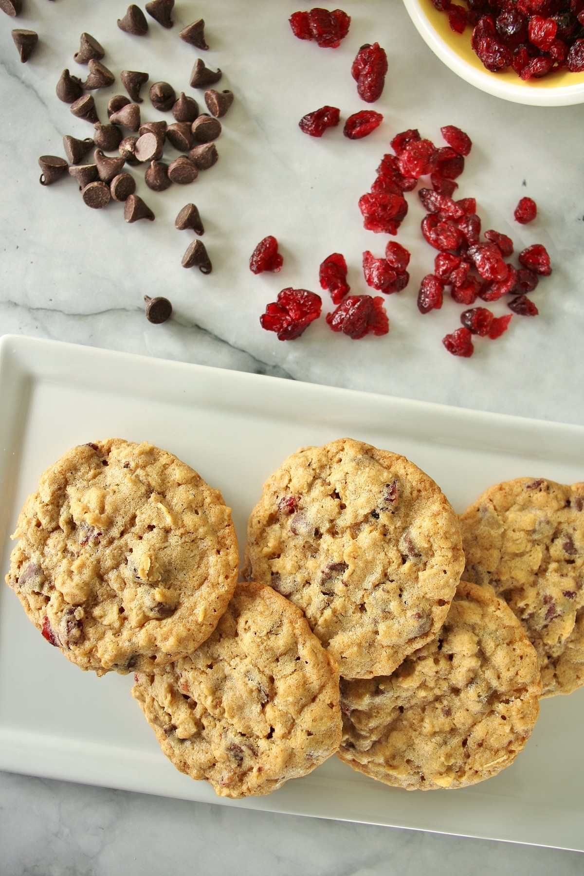 Five cranberry chocolate chip oatmeal cookies on a rectangular white plate