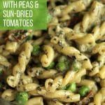 creamy pesto pasta salad with peas and sun-dried tomatoes in a glass serving bowl