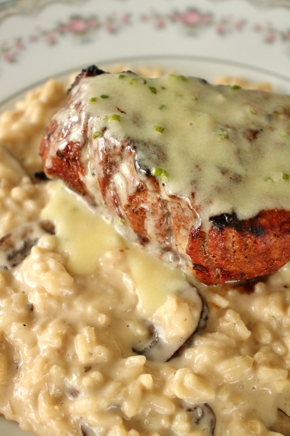Closeup of a filet mignon steak over a bed of mushroom risotto with truffle butter sauce