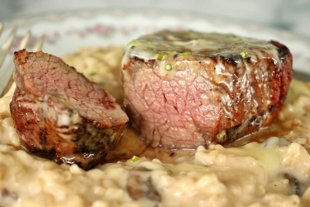 Closeup of a filet mignon steak over a bed of mushroom risotto. The steak is topped with a truffle butter sauce, and is sliced to show the medium-cooked center.