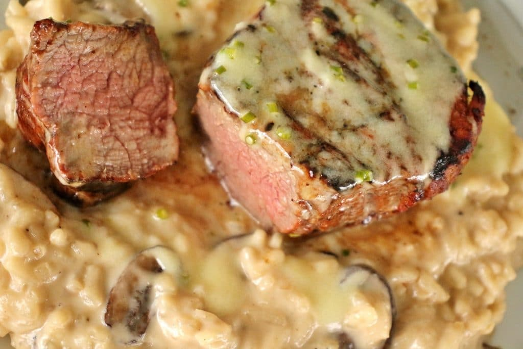 Le Cellier filet mignon steak over a bed of mushroom risotto. The steak is topped with a truffle butter sauce, and is sliced to show the medium-cooked center.