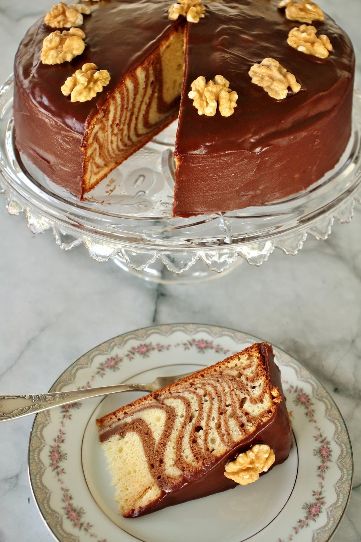 A chocolate glazed zebra cake on a crystal cake pedestal, with a slice of cake on a china plate next to it