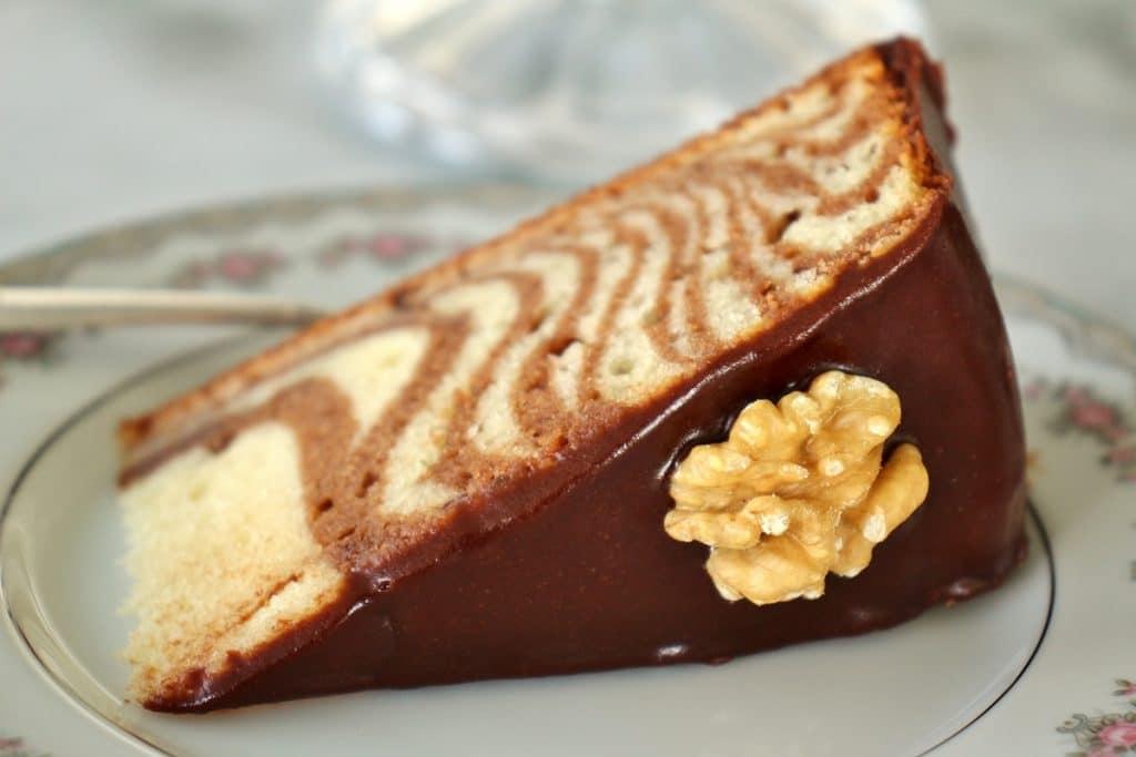 Close up of a slice of zebra cake with chocolate glaze and a walnut half garnish