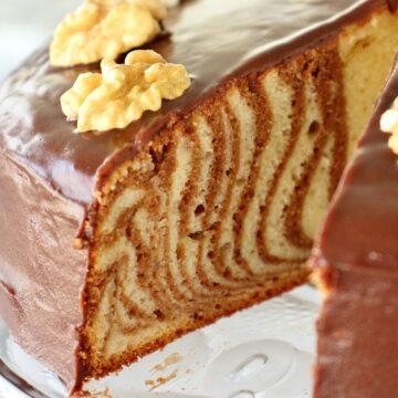 zebra cake with chocolate glaze, with slice removed