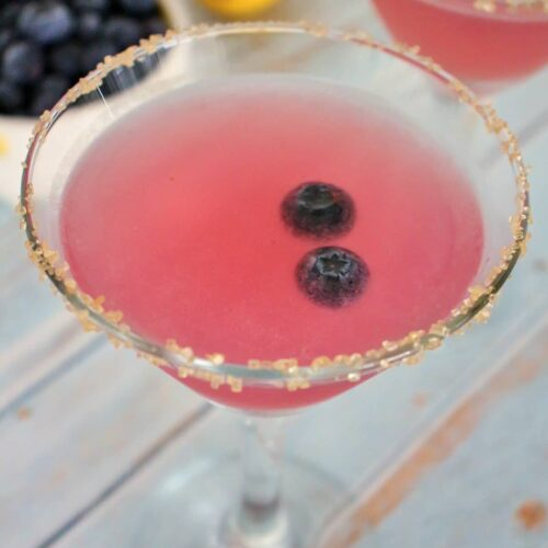 2 blueberry lemon drop martinis with a bowl of blueberries and fresh lemon in the background
