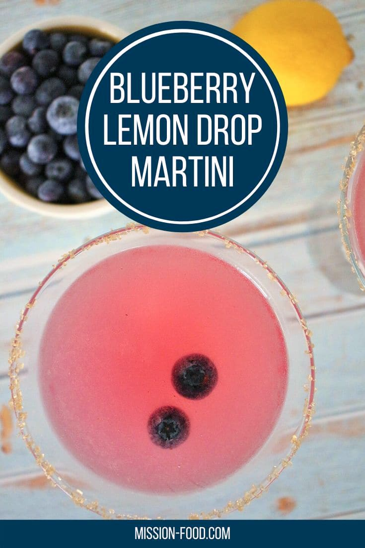 Overhead view of 2 blueberry lemon drop martinis with a bowl of blueberries and fresh lemon to the side