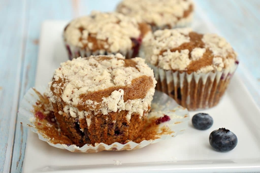 4 blueberry muffins with streusel topping on a white plate with blueberries scattered around them. One of them has the muffin liner peeled off.