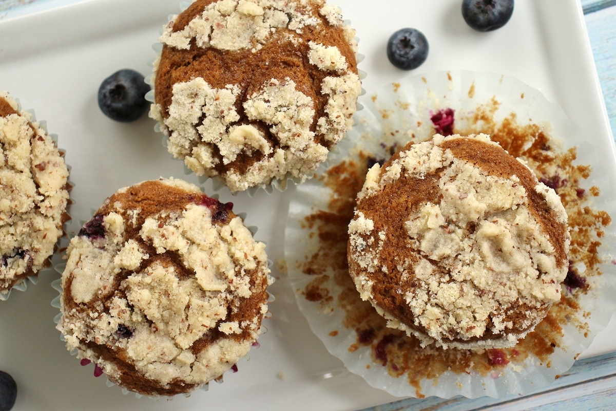 4 blueberry muffins with streusel topping on a white plate with blueberries scattered around