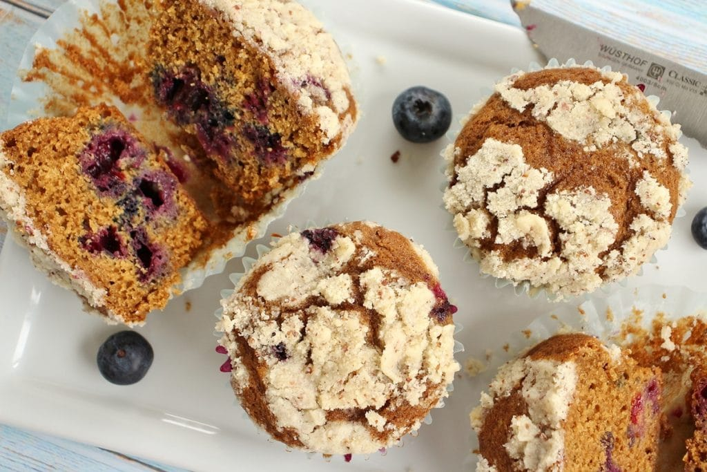 4 blueberry muffins with streusel topping on a white plate with blueberries scattered around them. 2 of the muffins are cut in half.