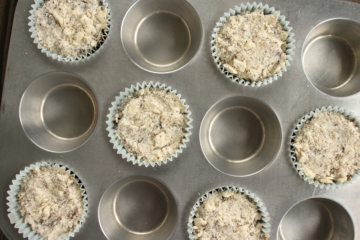 6 muffins with streusel topping arranged in a muffin pan before baking