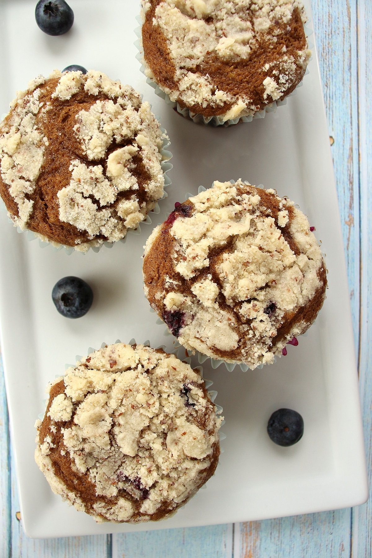 4 blueberry muffins on a white rectangular plate