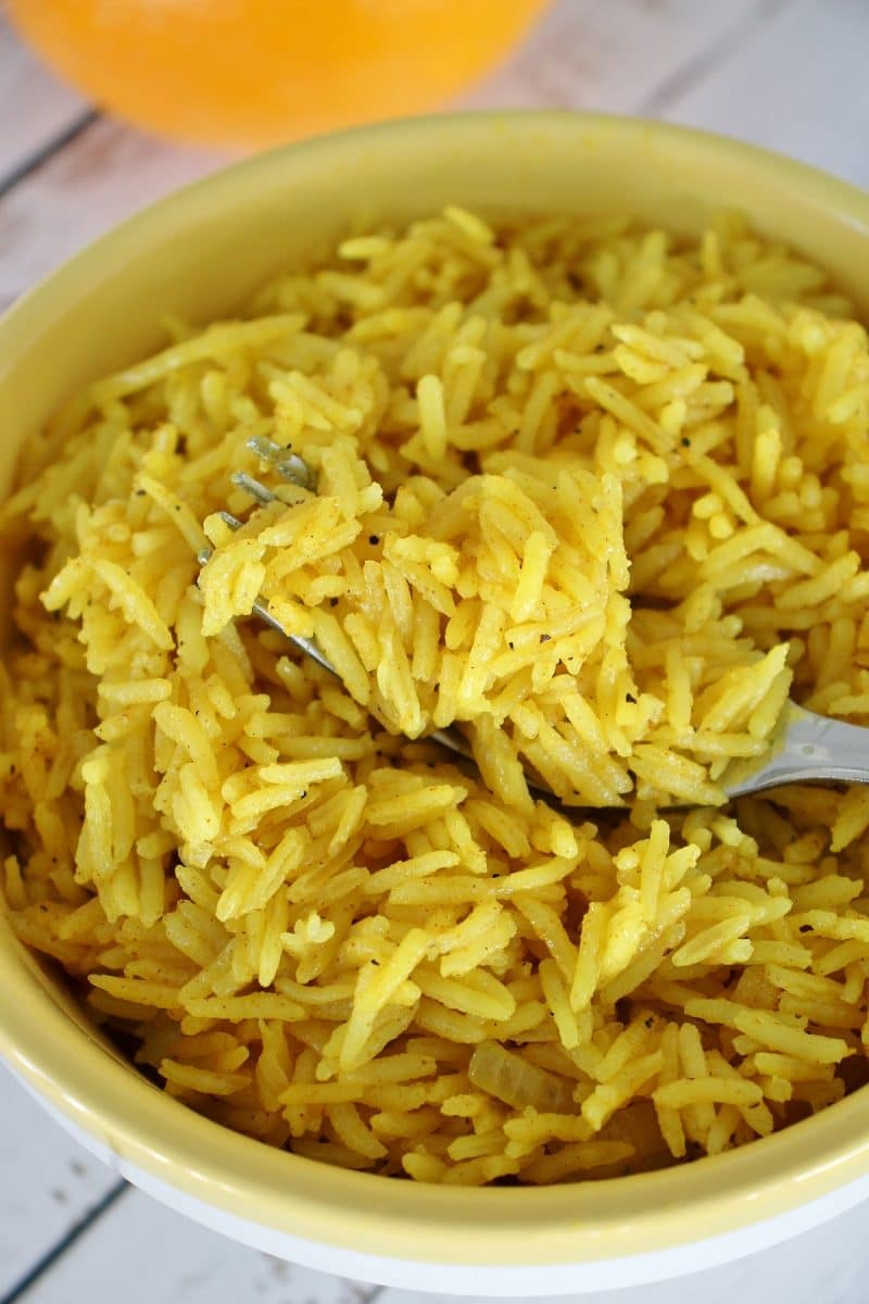 A bowl of Caribbean curried citrus rice with a fork scooping some up