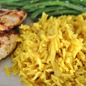 closeup of curried rice pilaf with onions, served with grilled chicken and green beans
