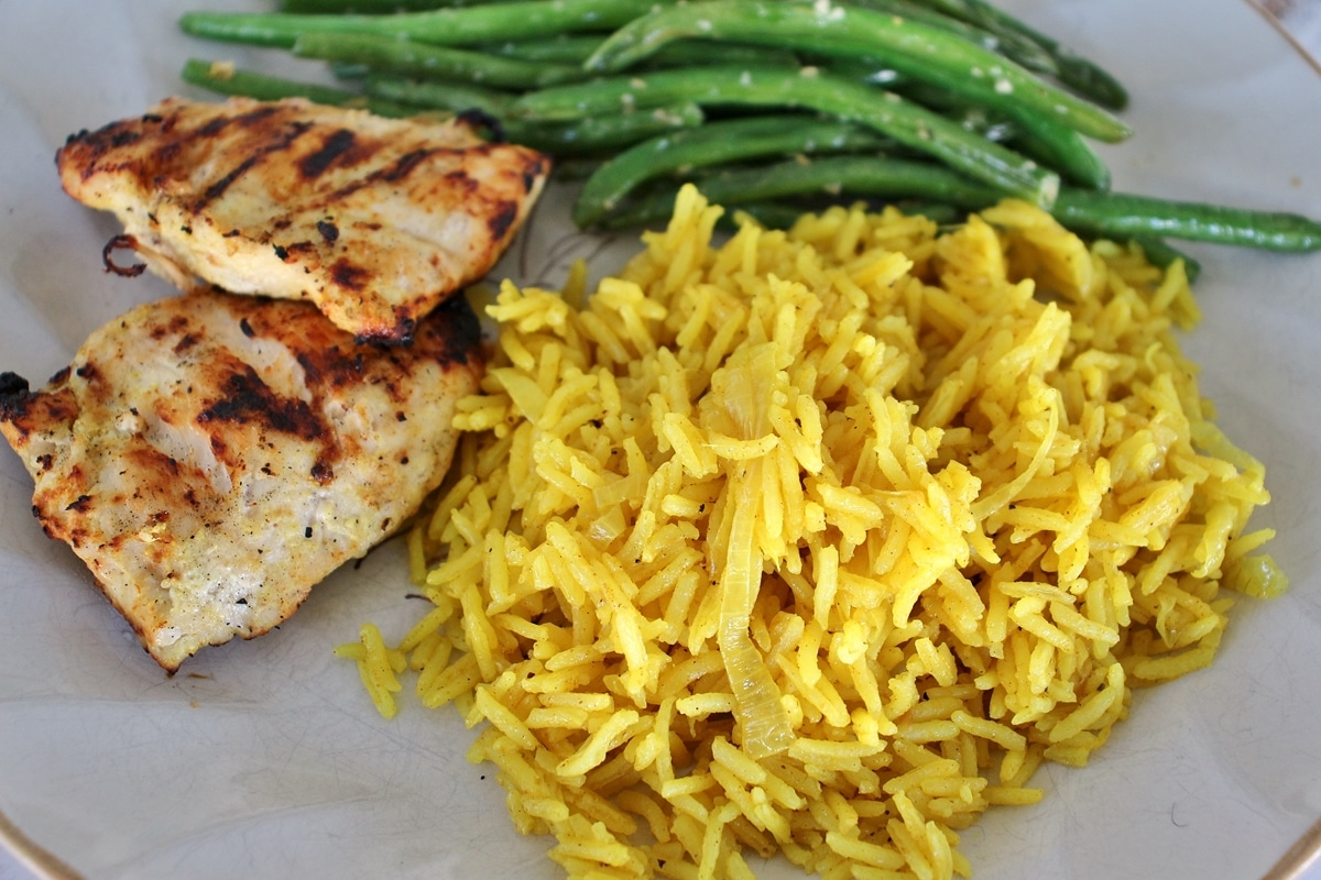 A plate of grilled chicken breast, green beans, and curried citrus rice