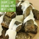 Dolma (stuffed grape leaves) drizzled with yogurt sauce on an antique pink plate