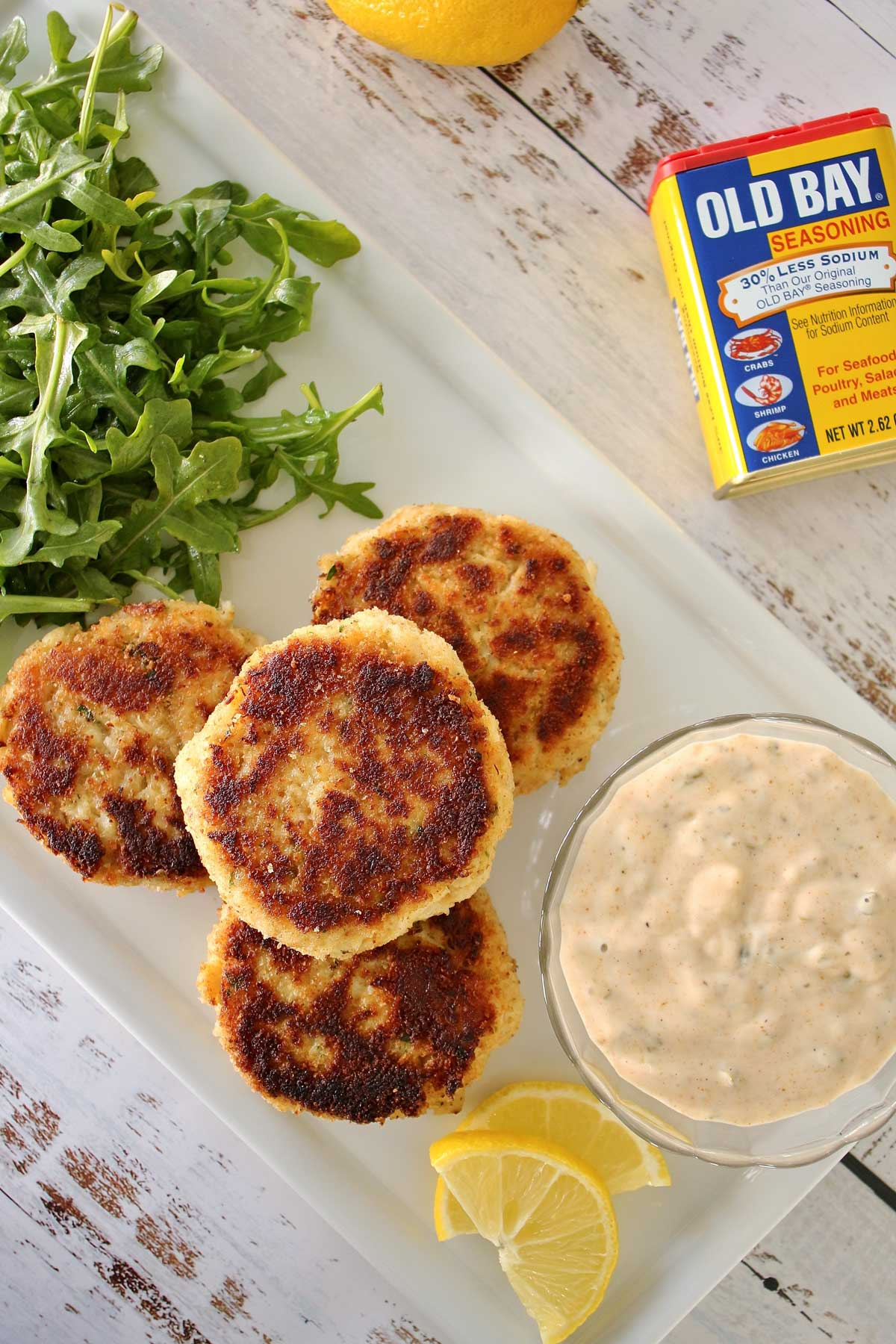 Four golden crab cakes on a white plate a bowl of sauce on one side, and an arugula salad on the other. A can of Old Bay Seasoning and a lemon are on the table next to it.