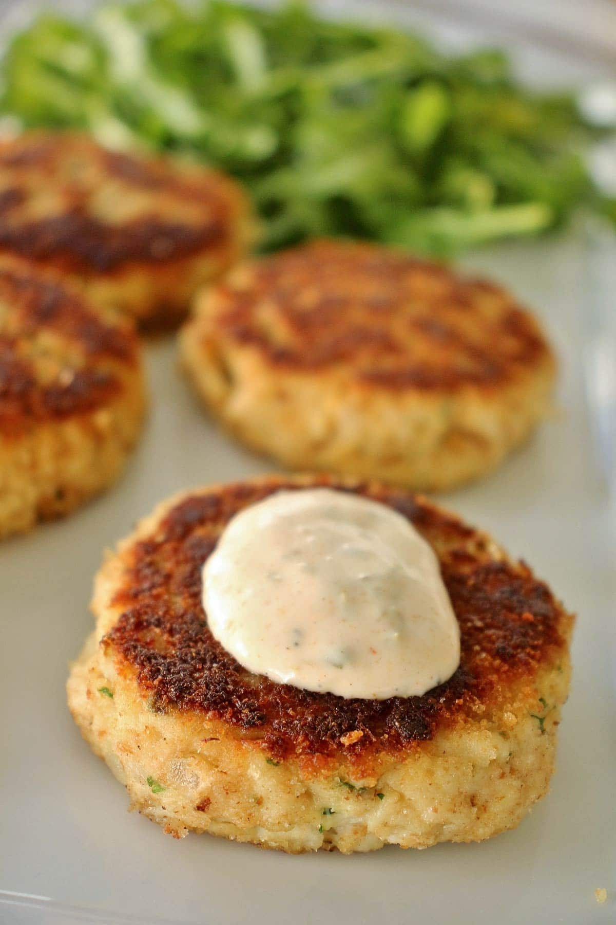 Four golden crab cakes on a white plate with a dollop of sauce on one.