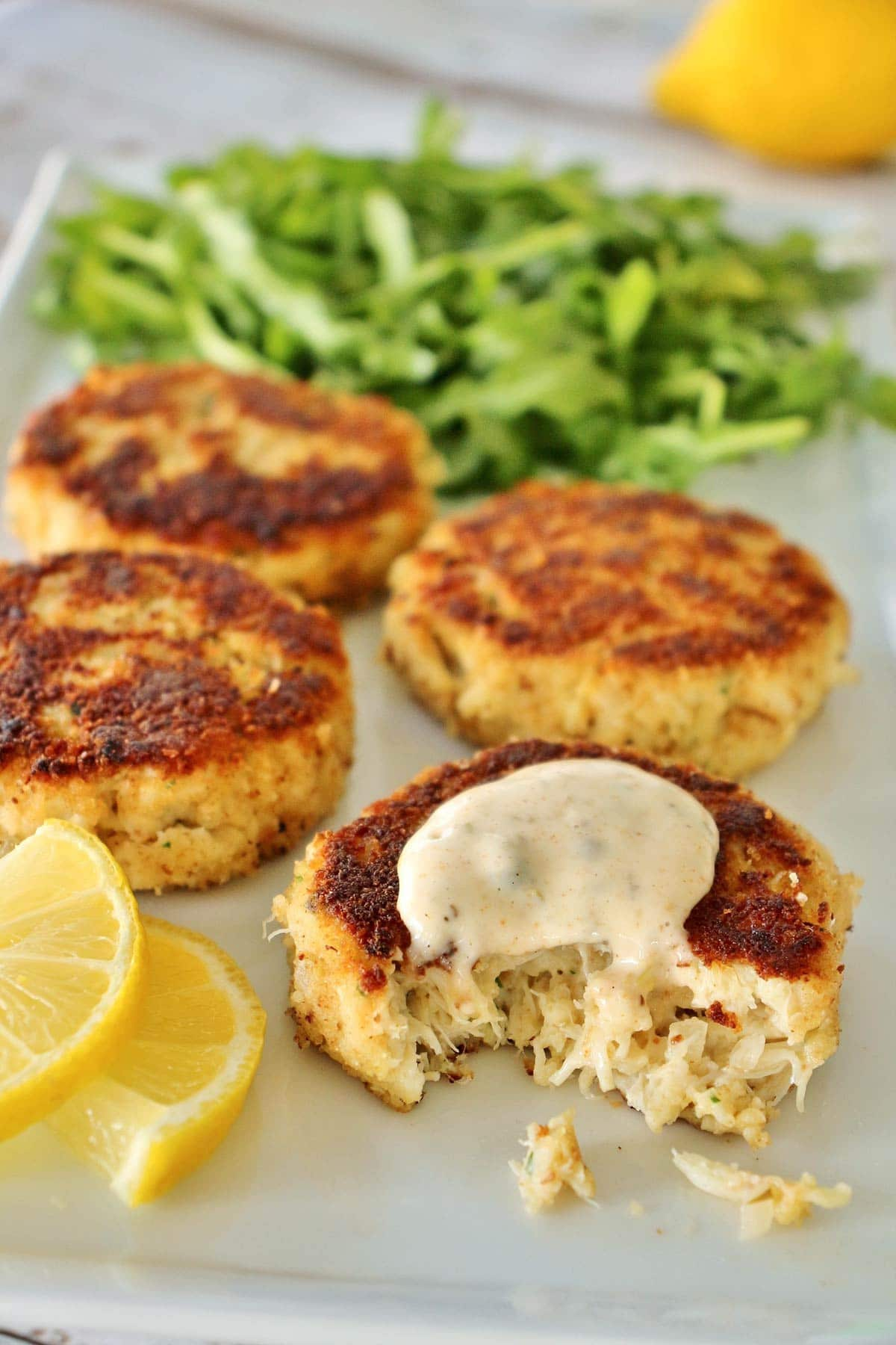 4 crab cakes with lemon slices and arugula on white plate