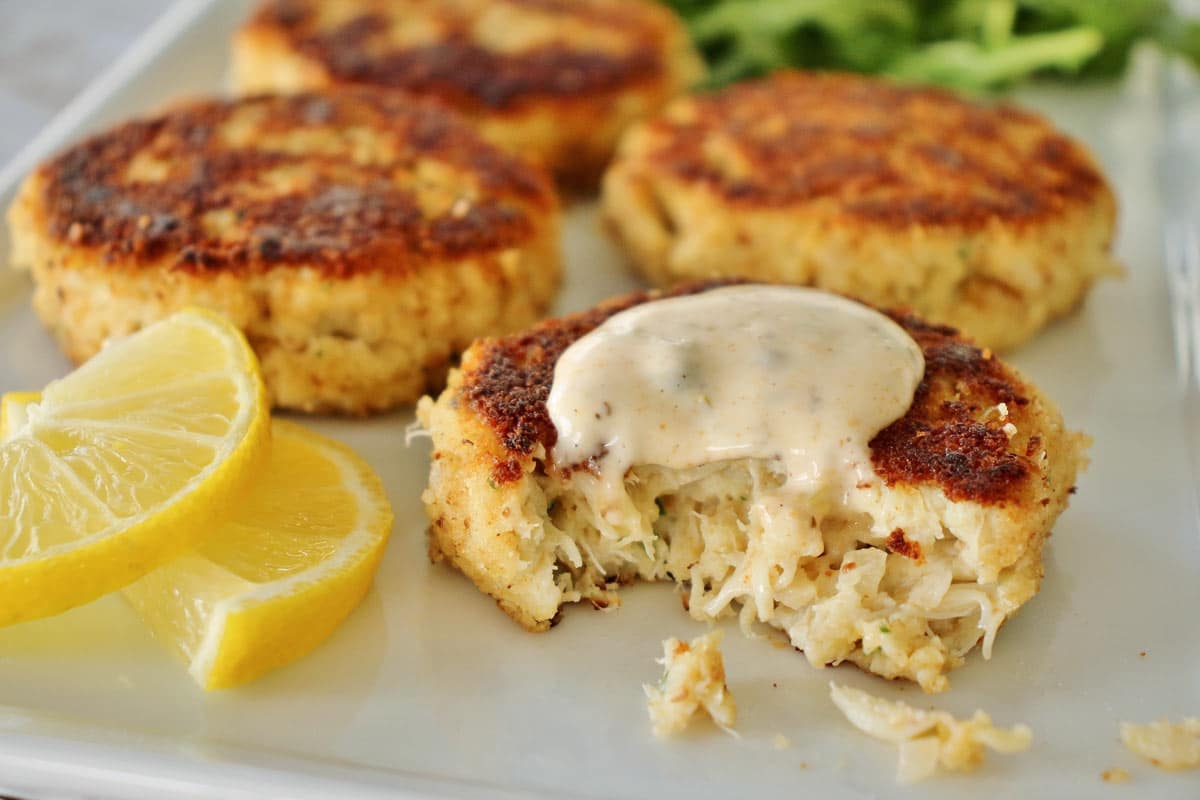 Four golden crab cakes on a white plate with a dollop of sauce on one with a bite taken out.