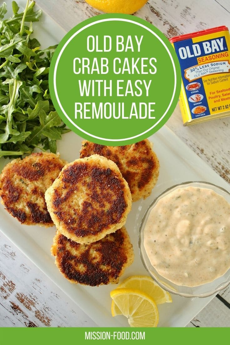 4 crab cakes on a rectangular plate with sauce and salad