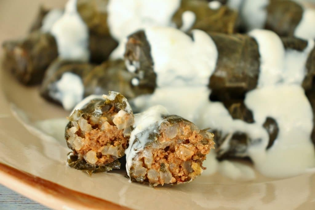 Dolma (grape leaves) drizzled with yogurt and garlic sauce on an antique pink plate; one is cut open to show the inside