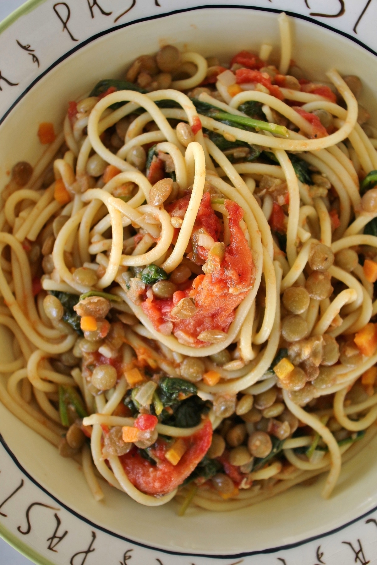 A bowl of spaghetti with lentils, roasted tomatoes, and spinach