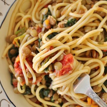 spaghetti with lentils, roasted tomatoes, and spinach twisted around a fork