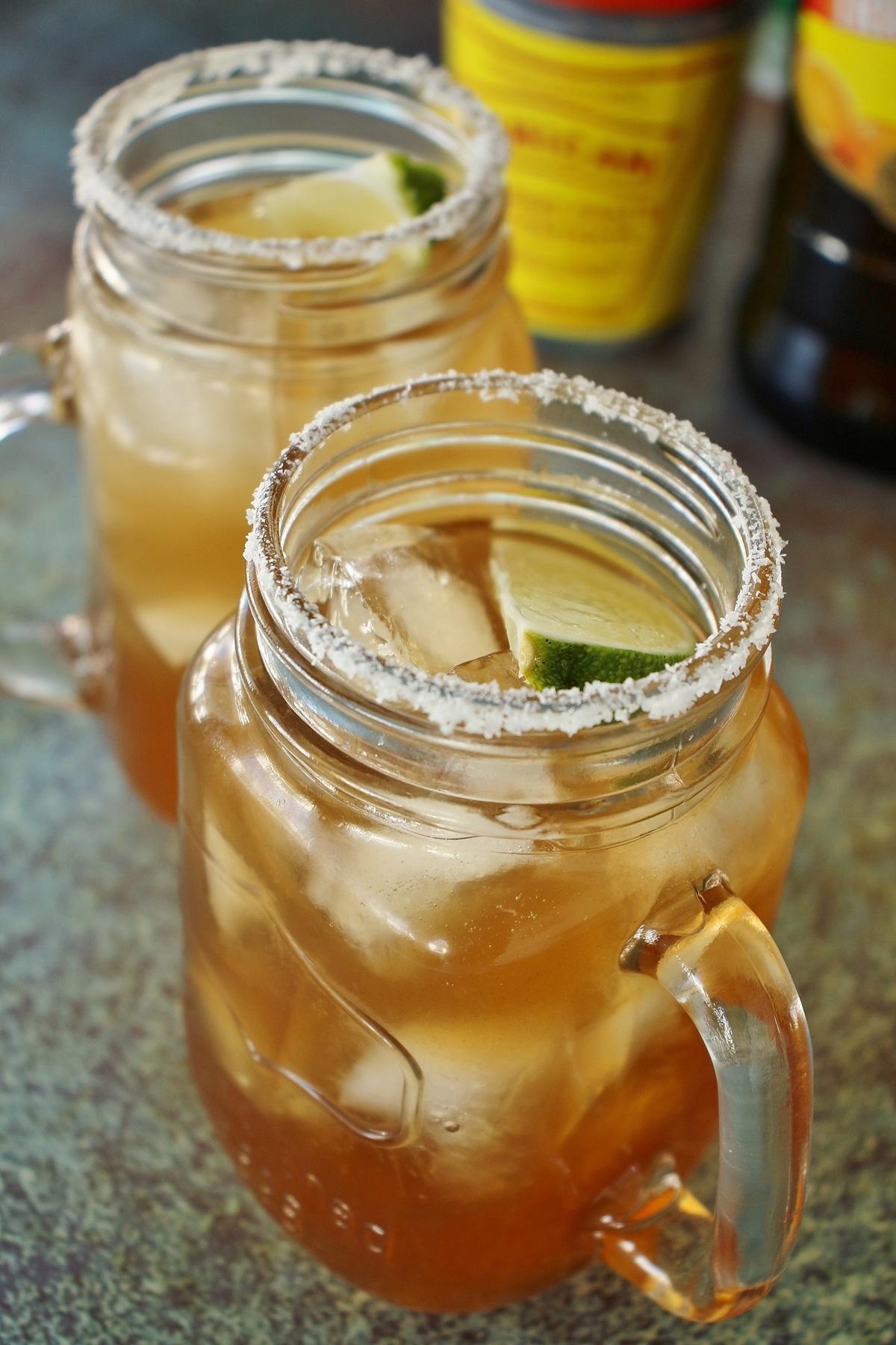 2 tamarind margaritas with salt rims and lime wedge garnish, served in mason jar mugs