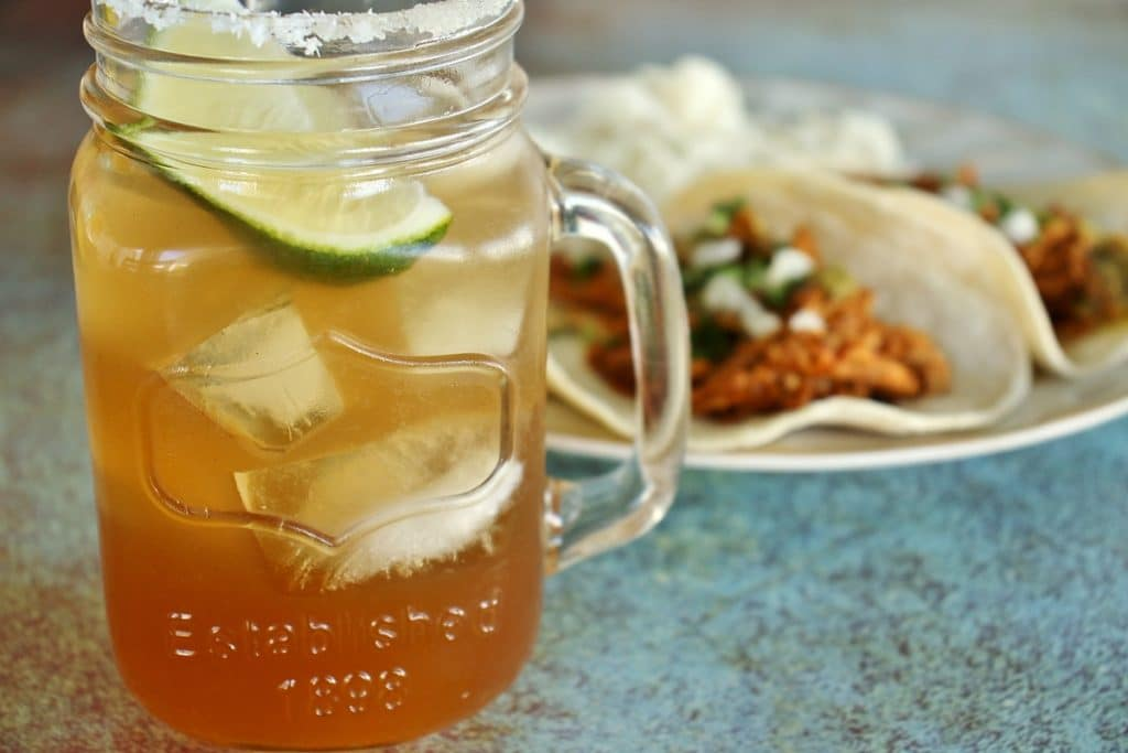 A tamarind margarita served in a mason jar mug, with a plate of tacos in the background