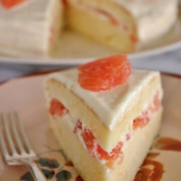 A slice of grapefruit cake on an antique plate with the full cake in the background
