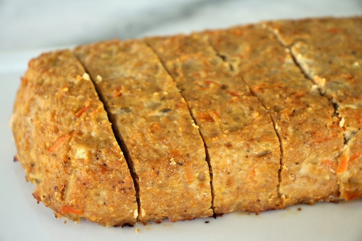 turkey meatloaf on a white cutting board sliced into servings