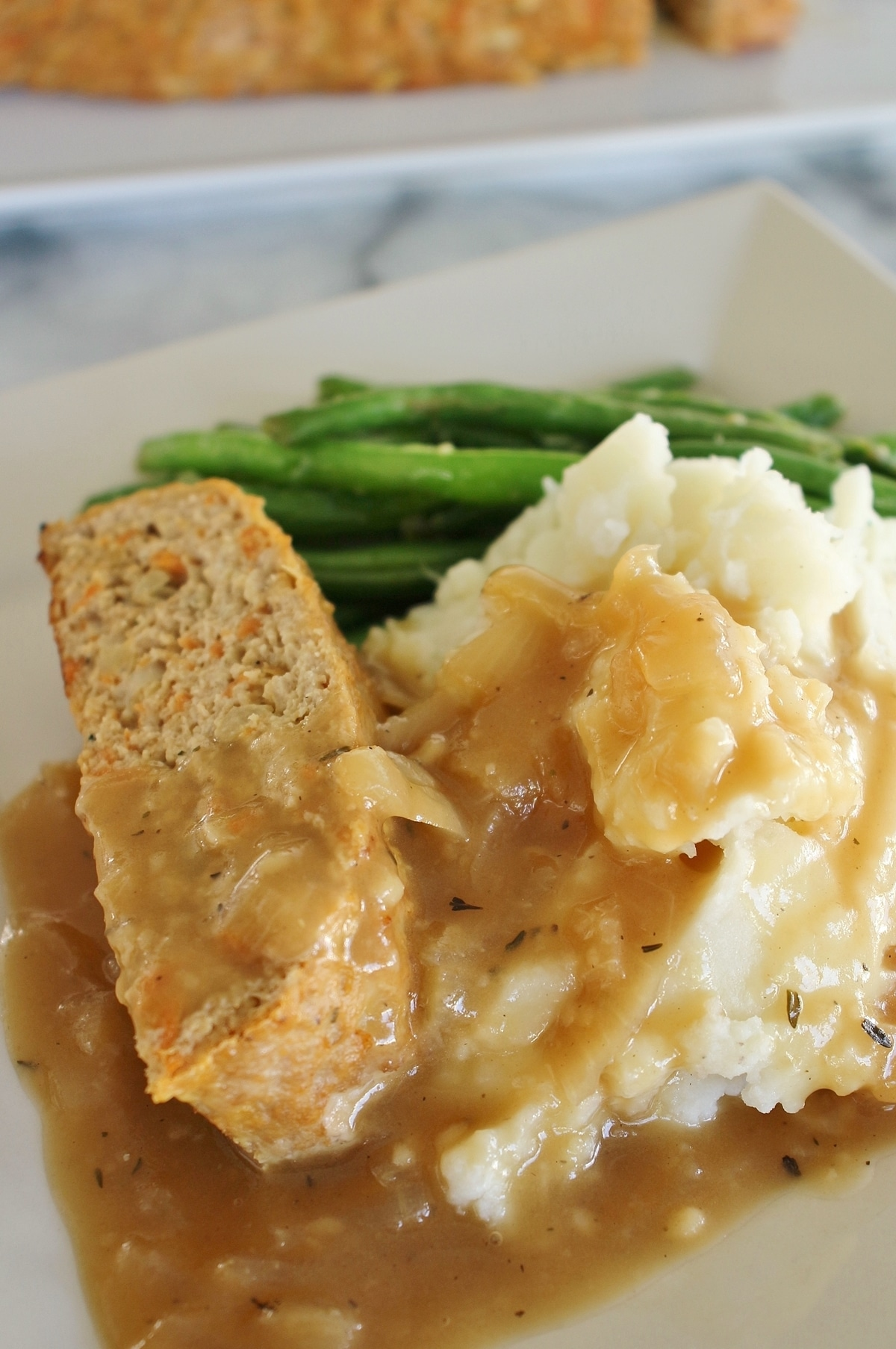 side view of turkey meatloaf with onion gravy, mashed potatoes and green beans