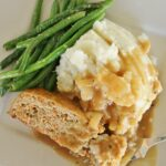 turkey meatloaf with onion gravy, mashed potatoes, and green beans on a square plate