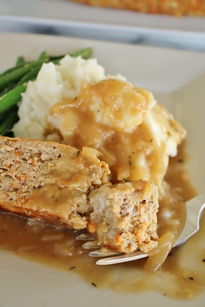 close up of turkey meatloaf with onion gravy, mashed potatoes and green beans, with a piece broken off by a fork