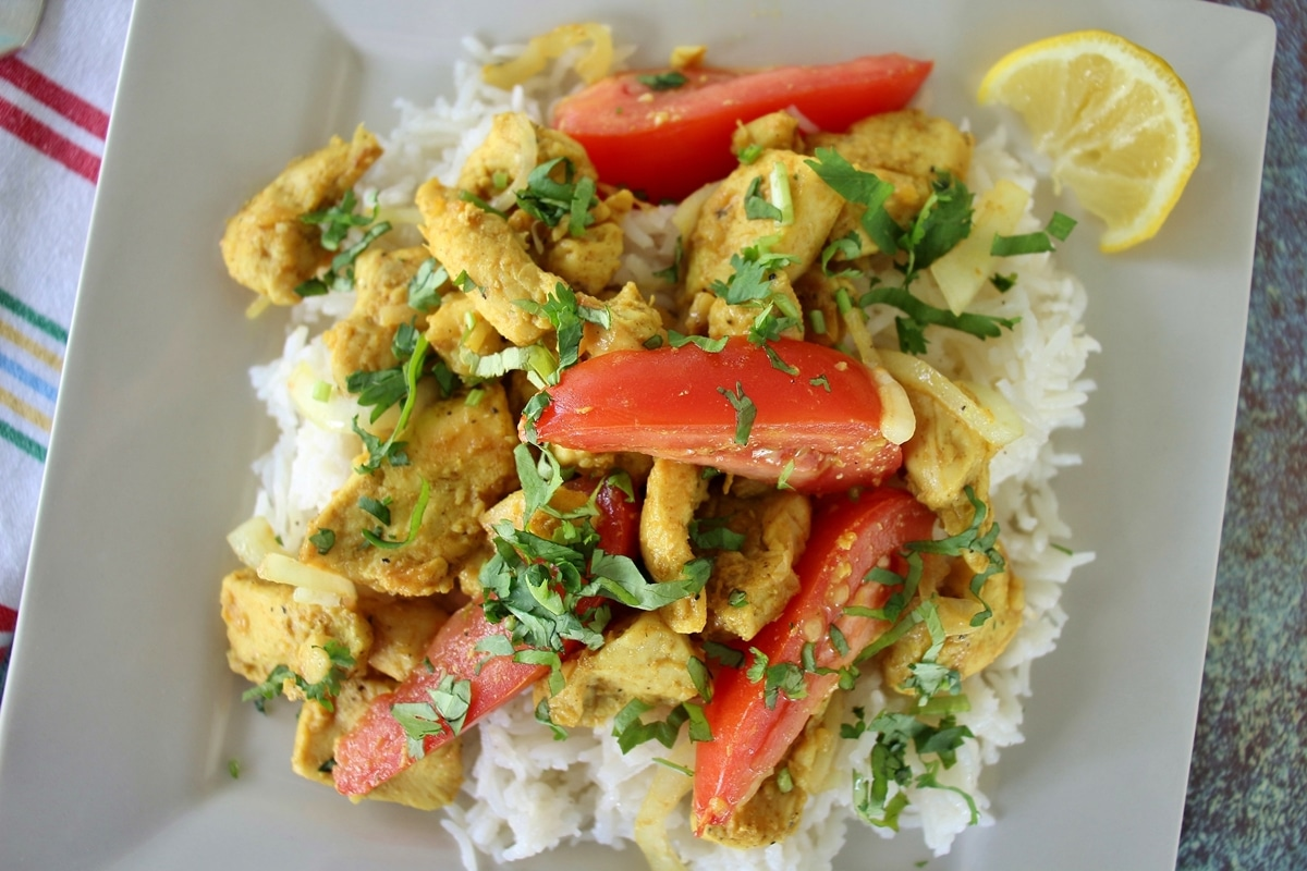 Burmese chicken kebat stir-fry with cilantro and tomatoes on a square plate