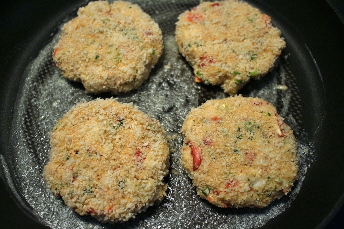 4 lobster cakes cooking in a nonstick skillet