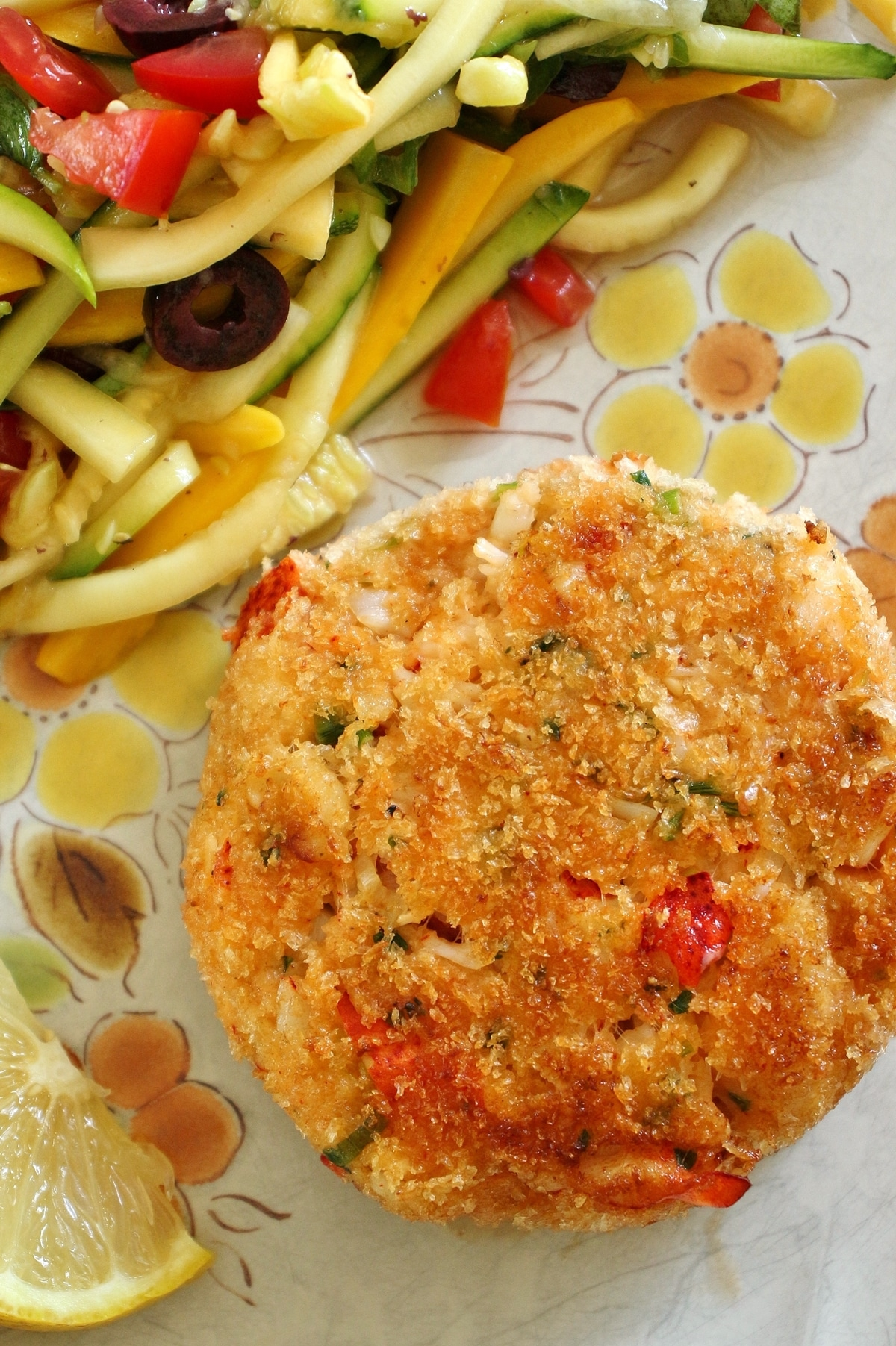 closeup of a lobster cake on a vintage plate with zucchini slaw on the side
