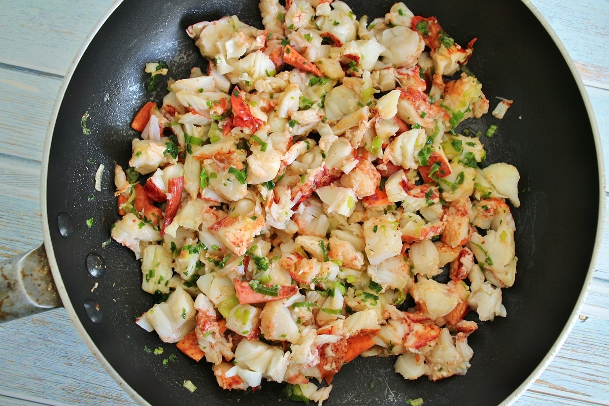 a combination of lobster meat, scallions, and seasonings in a nonstick skillet