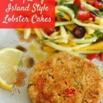a lobster cake on an antique plate with a lemon wedge and zucchini slaw
