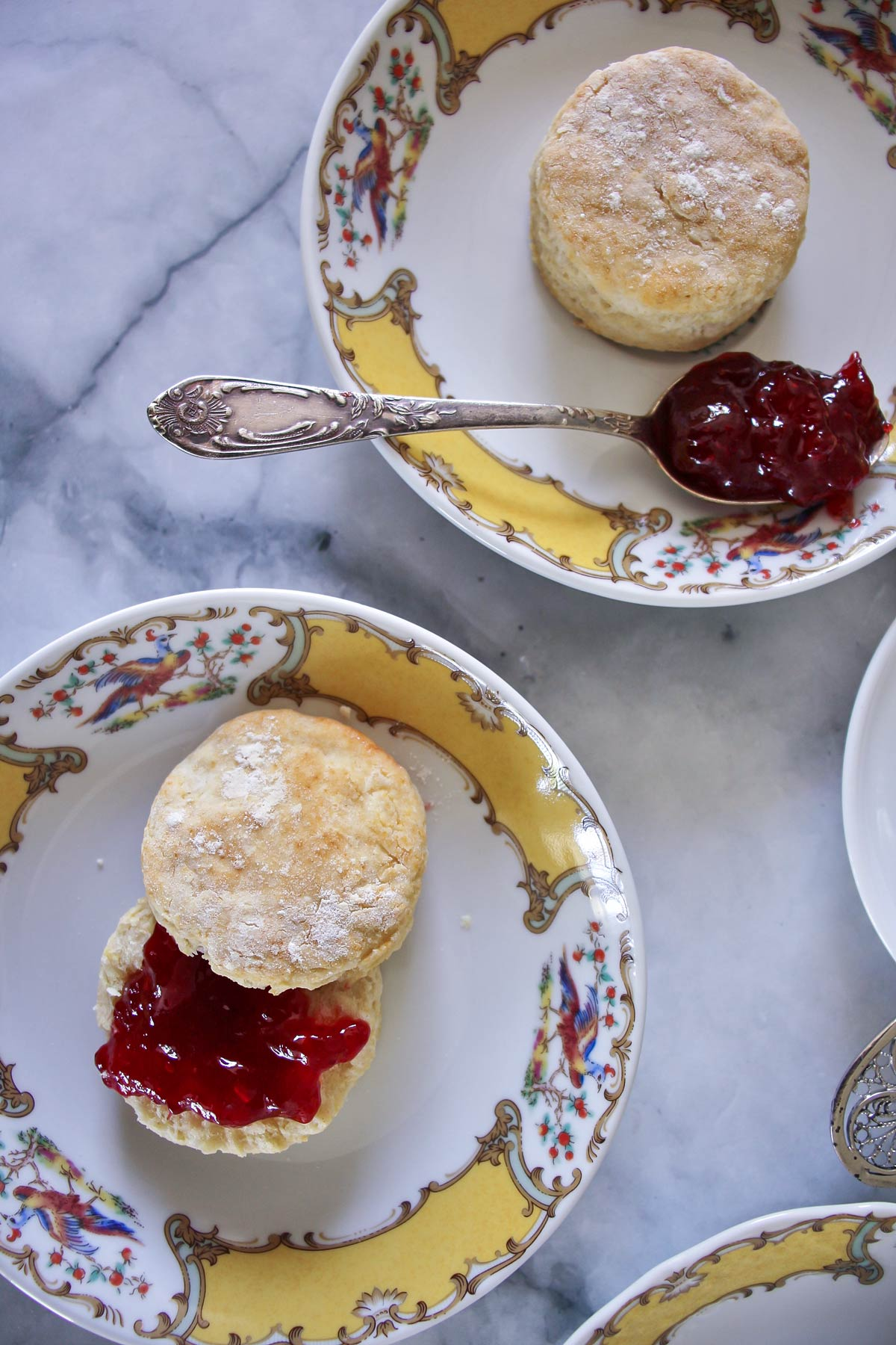 Two dainty afternoon scones served on yellow and white fine china, with strawberry jam