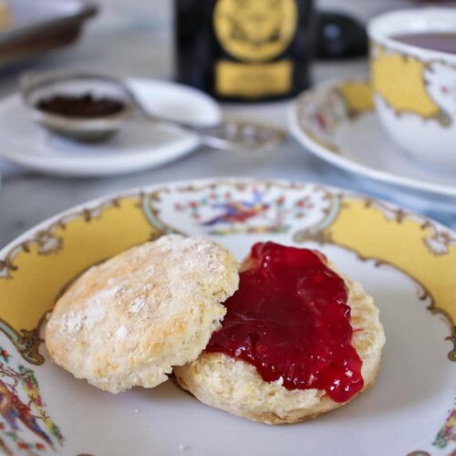 a tea scone topped with strawberry jam, served on fine china with a cup of tea in the background
