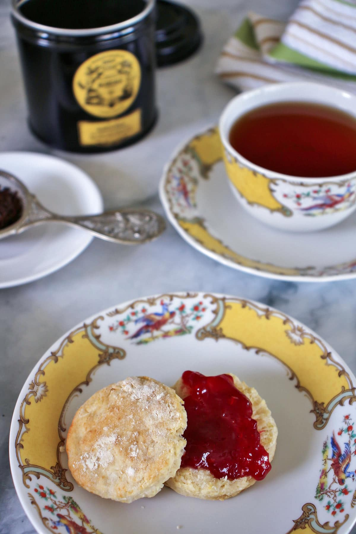 A small British afternoon tea scone topped with strawberry jam, served with a cup of tea in fine china
