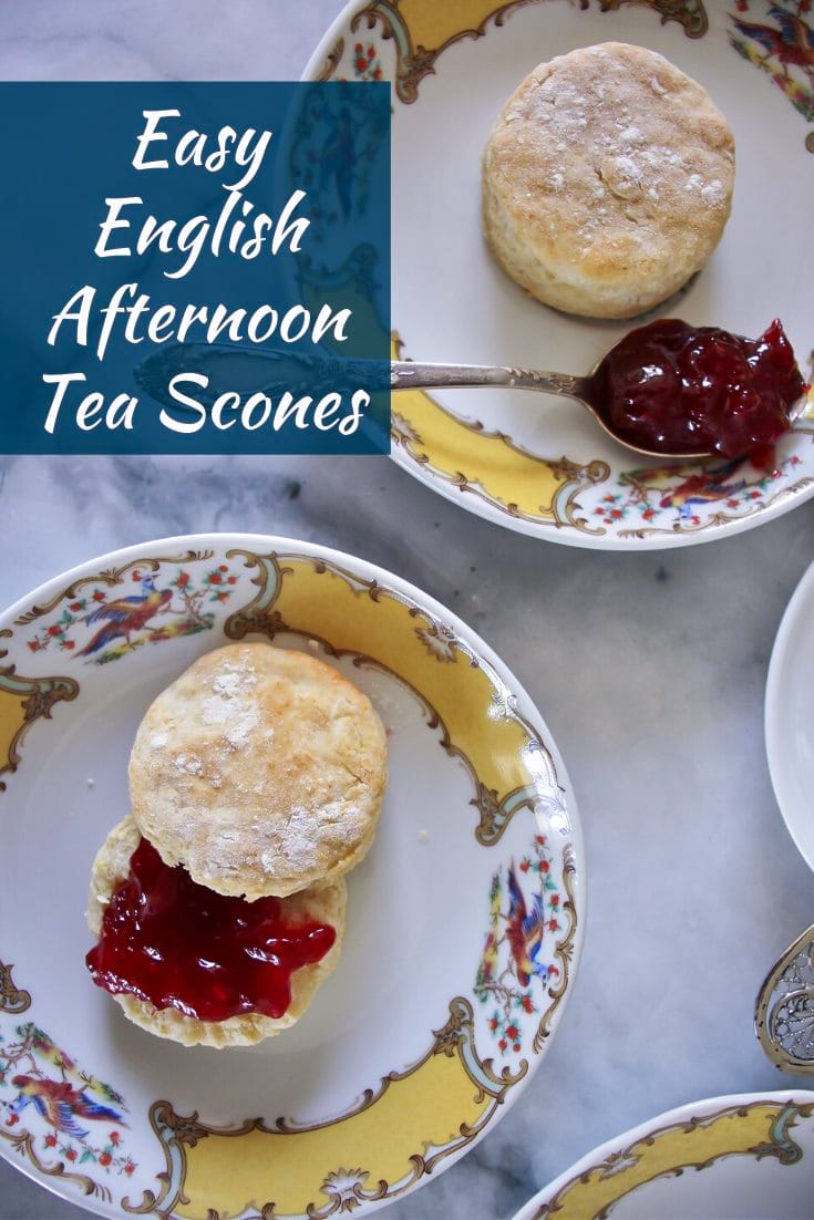 two English scones served on fine yellow and white china with spoonfuls of strawberry jam
